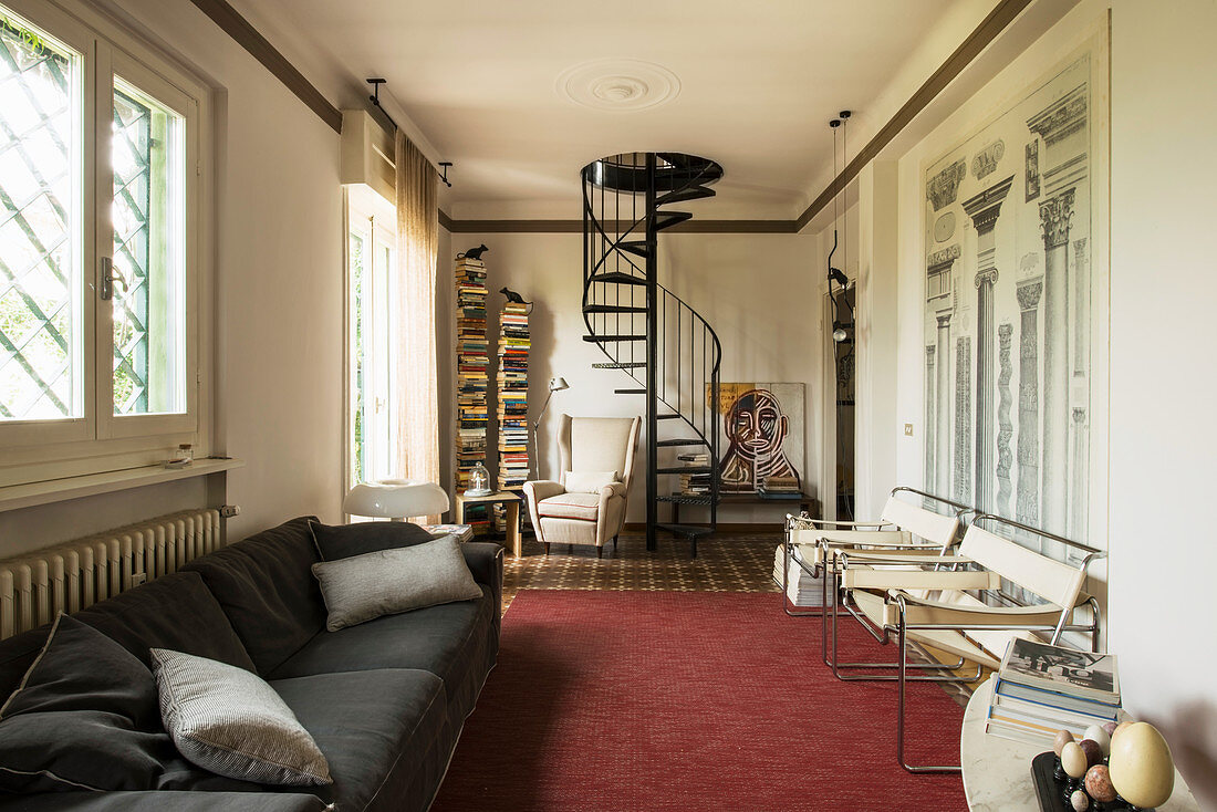 Spiral staircase and architectural diagram on wall in Italian-style living room
