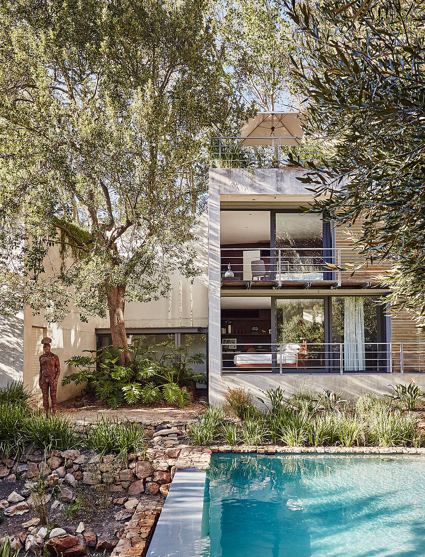 View from garden across pool to architect-designed house with balconies
