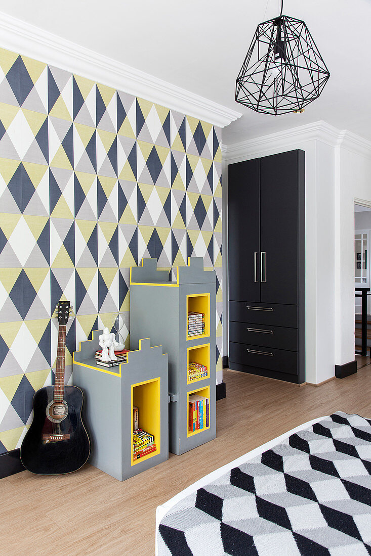 Modular shelves and guitar against geometric wallpaper and fitted wardrobe in teenager's bedroom