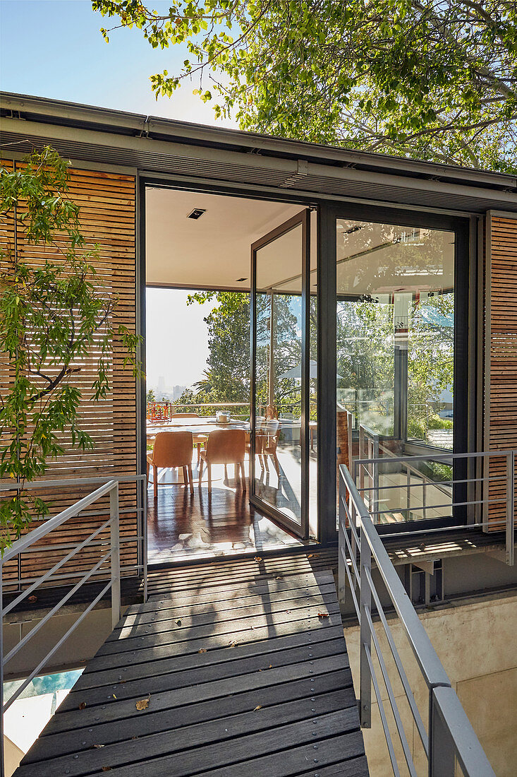 Walkway leading to modern architect-designed house with glass door opening into dining room