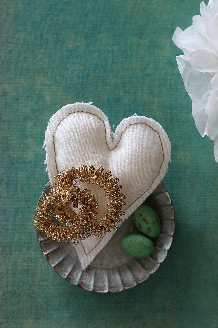 Golden wreaths on fabric heart in flan tin