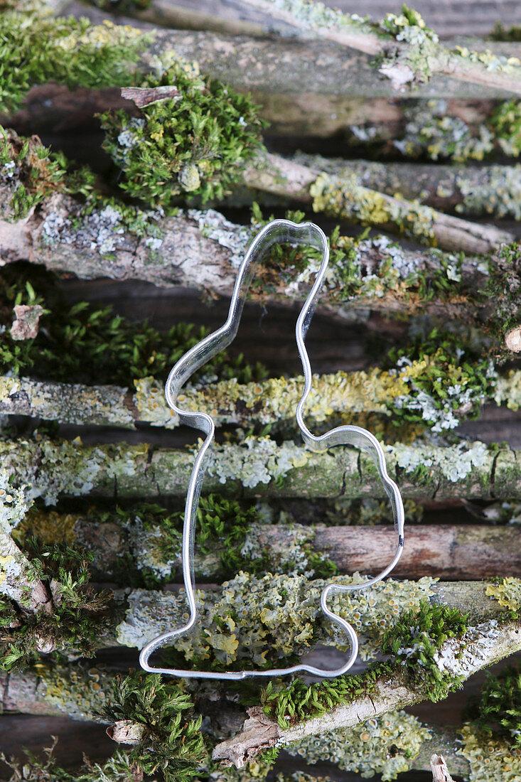 Ausstecher in Hasenform auf Zweigen mit Moos und Flechten