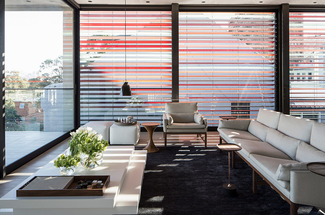 White designer sofa in front of all-round window front with aluminum blinds