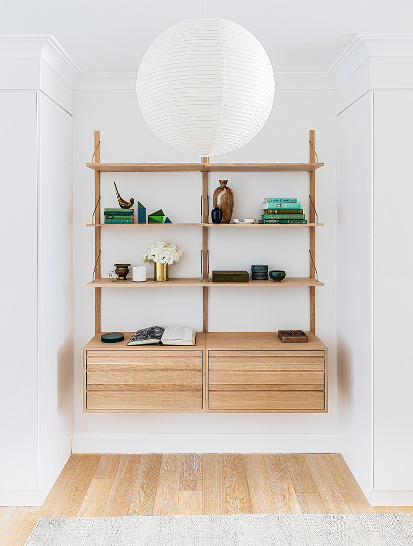 Shelf system with decorative objects, flower vase and books in a wall niche, in front of it a white ball lamp