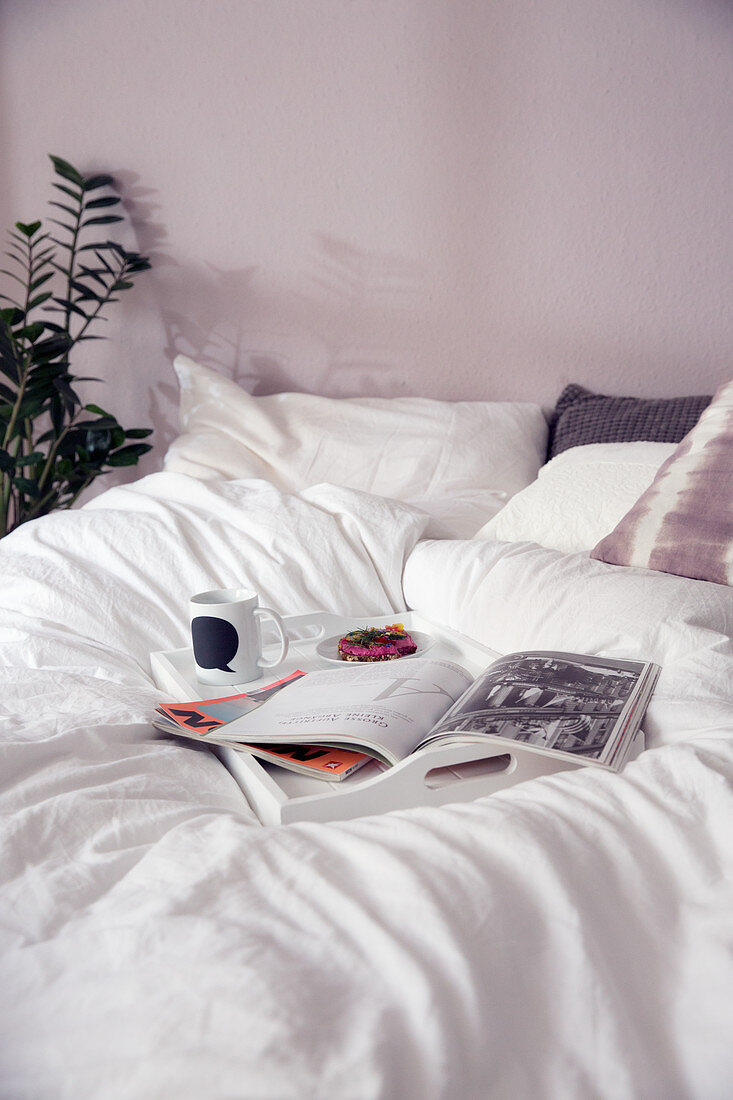 A breakfast tray with a newspaper on a bed