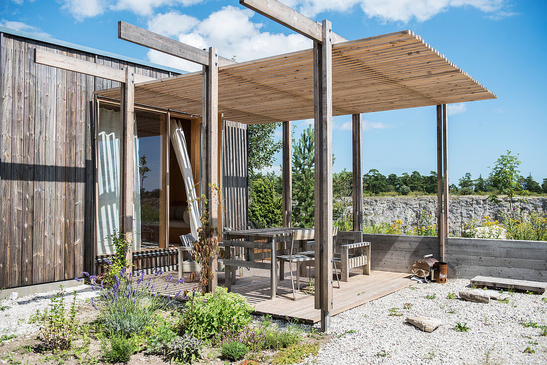 Roofed terrace adjoining simple wooden house below blue sky