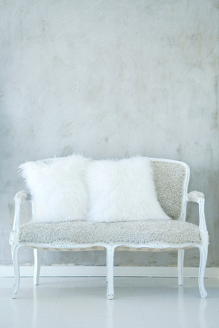 Baroque couch with plush upholstery and fur scatter cushions against white-mottled wall