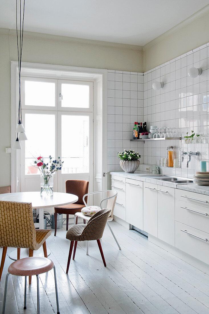 Various retro chairs at round table next to white kitchen counter