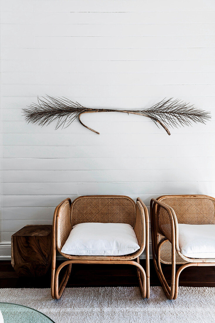 Designer rattan chairs with dried branches on white wall