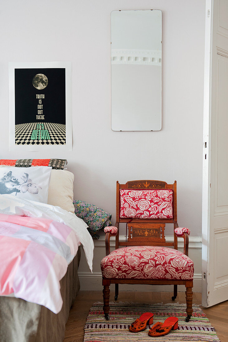 Antique chair with floral upholstery next to bed