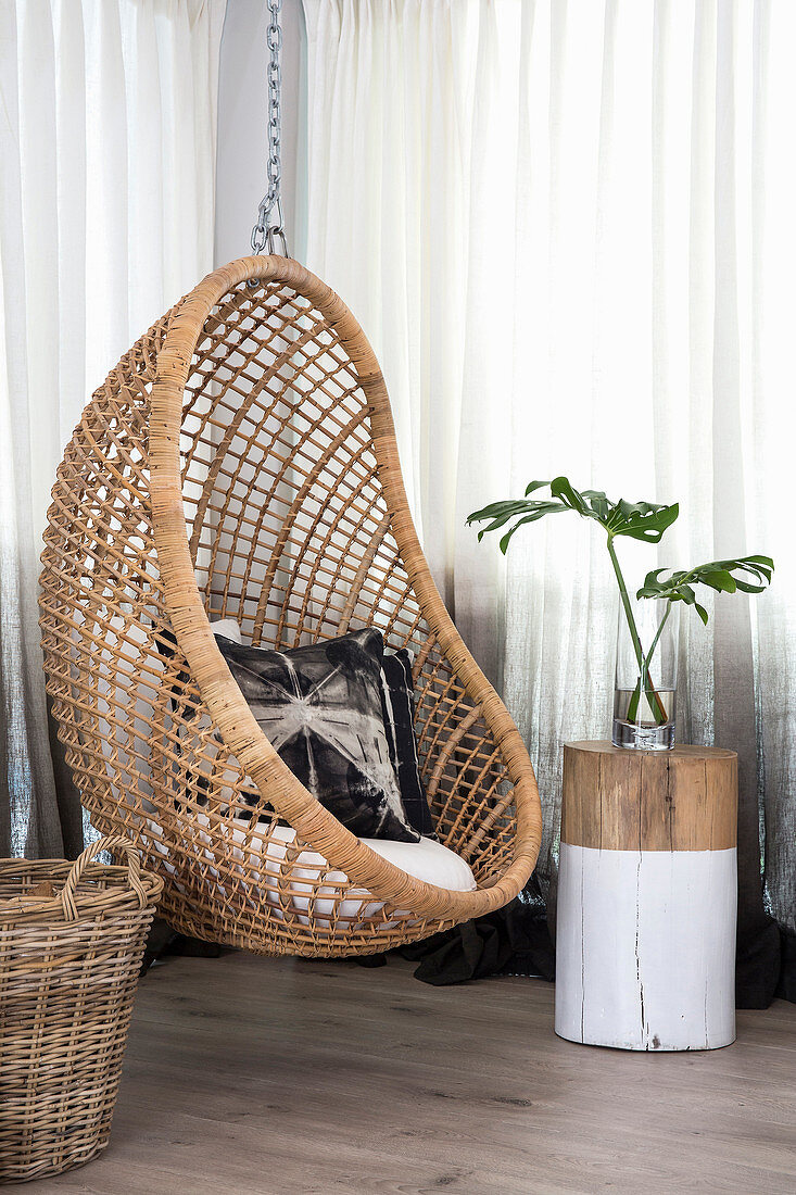 Hanging chair and tree-stump table in corner