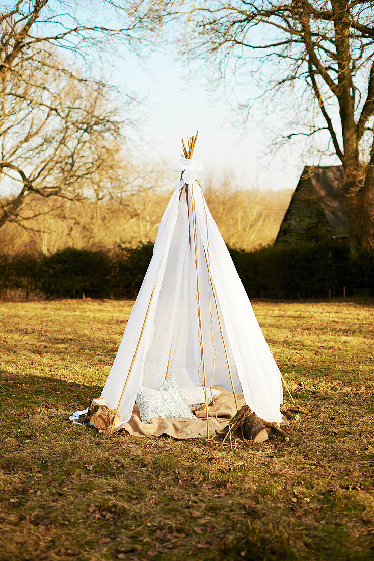 Cushions in hand-made teepee in autumnal garden