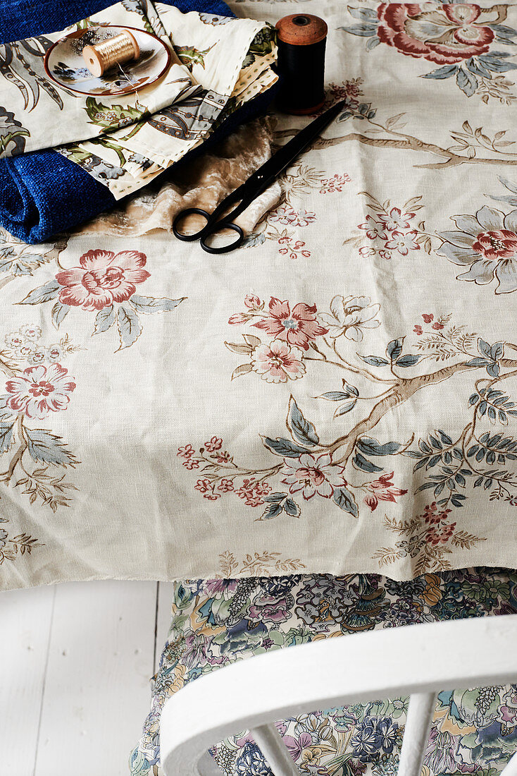 Sewing utensils on floral tablecloth