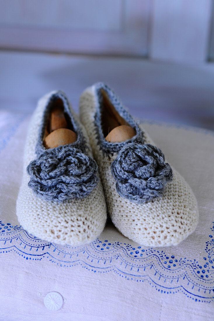 Gehäkelte Bettschuhe in Weiß mit blauer Häkelblüte