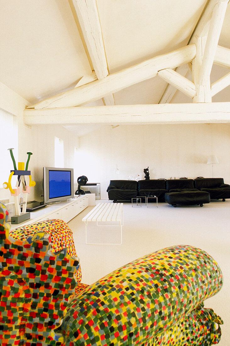 Multi-coloured armchair, TV cabinet and black sofa in bright attic living room