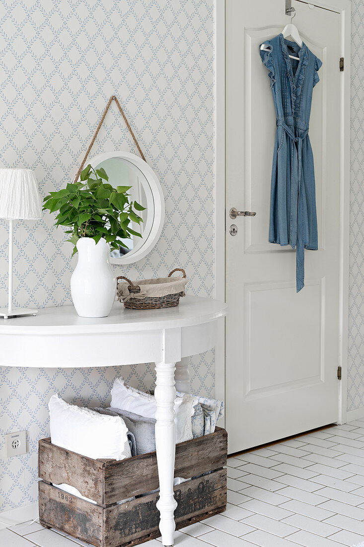 Semicircular console table against wall with diamond-patterned wallpaper