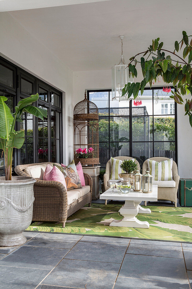 Wicker furniture and leaf-patterned rug on roofed terrace