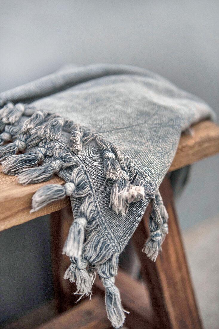 Grey tasselled peshtemal on wooden stool