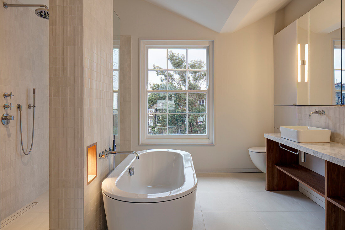 Free-standing bathtub against partition in modern bathroom