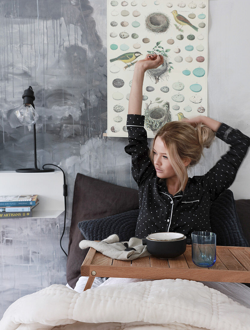Woman wearing pyjamas stretching in bed with breakfast tray