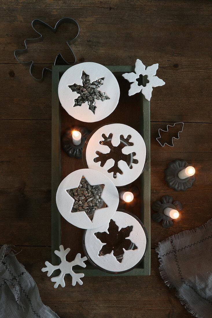 Kreise mit ausgestochenen Sternen und brennende Kerzen
