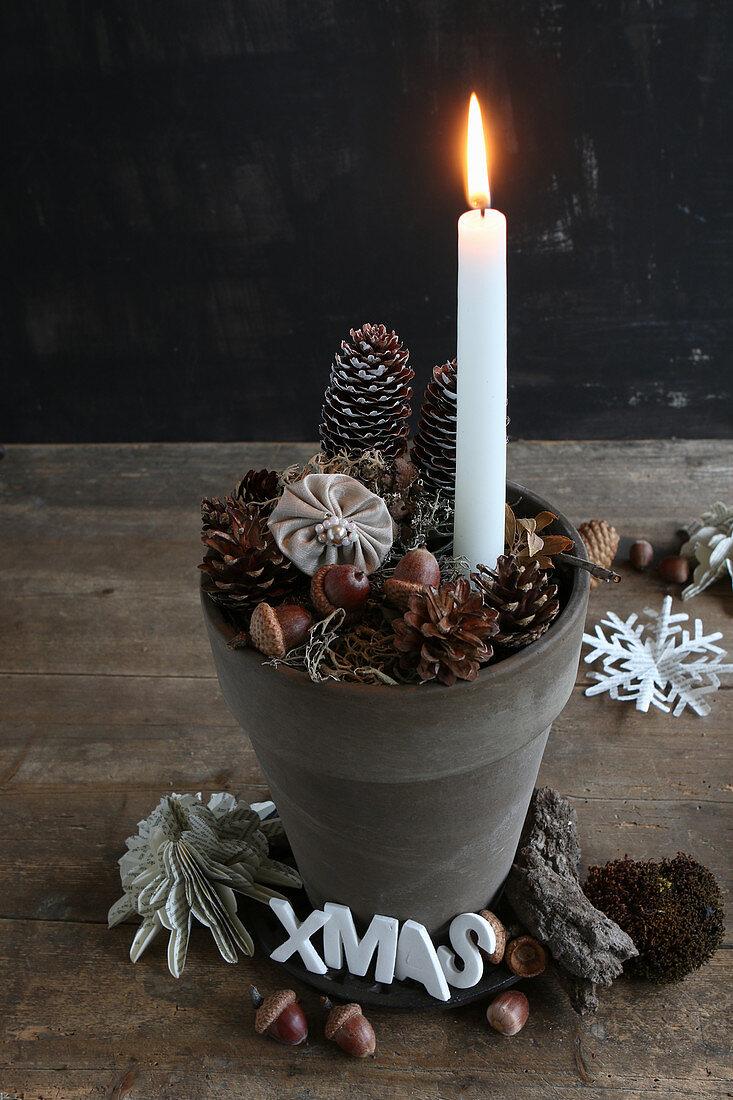 Brennende Kerze in einem Tontopf mit weihnachtlicher Deko