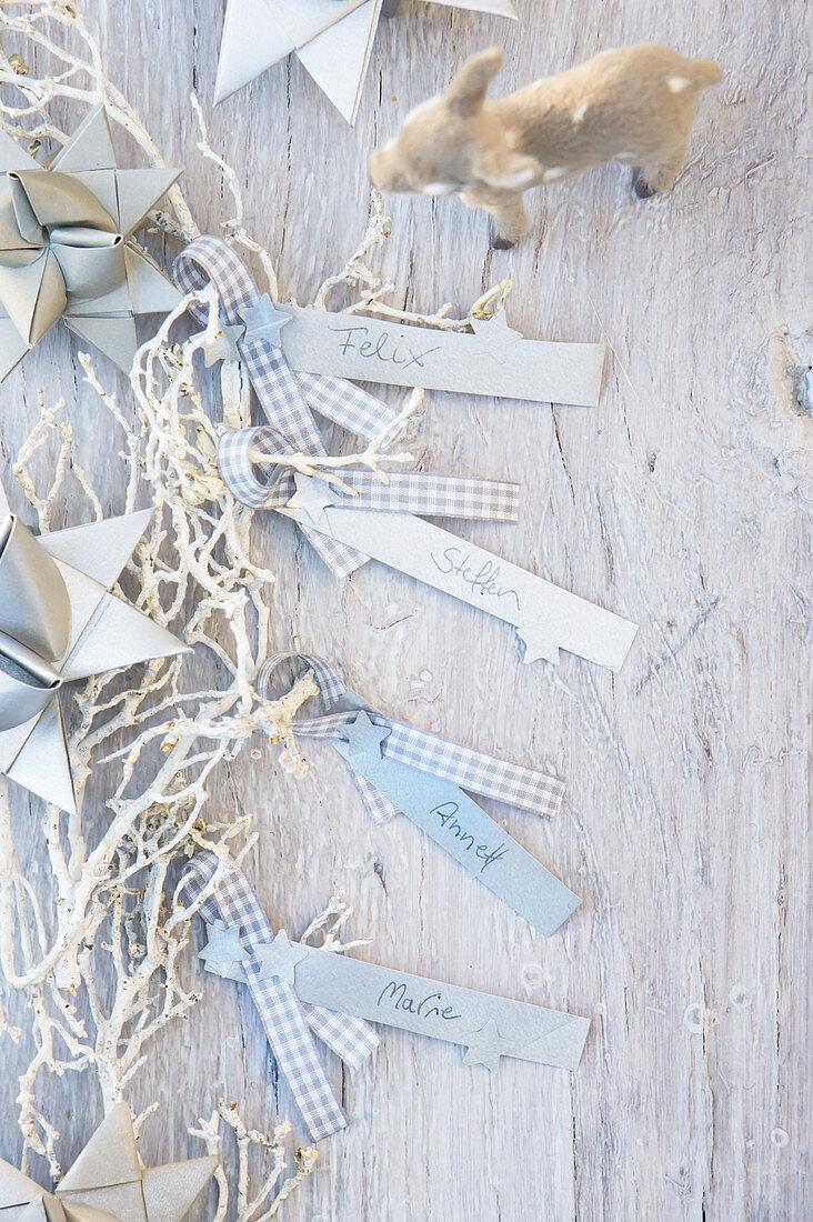 DIY-Namensschildchen zu Weihnachten aus Papierstreifen und kariertem Band, Papiersterne und Rehfigur