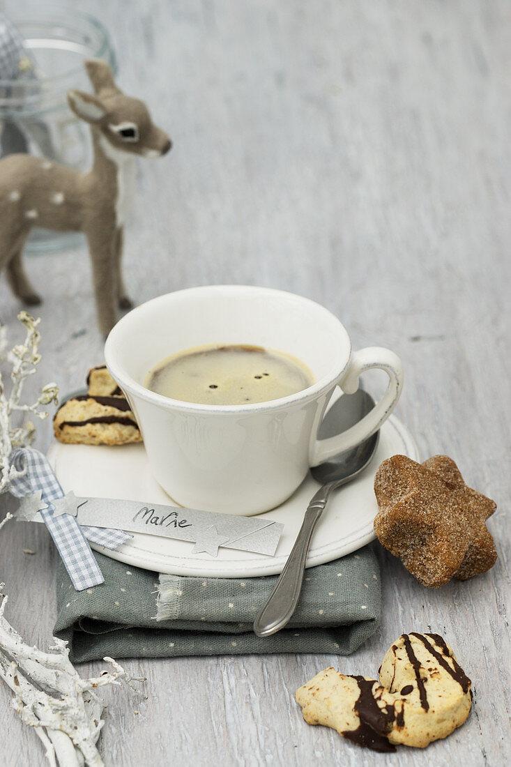 Eine Tasse Kaffee mit Plätzchen, DIY-Namensschildchen und Rehfigur