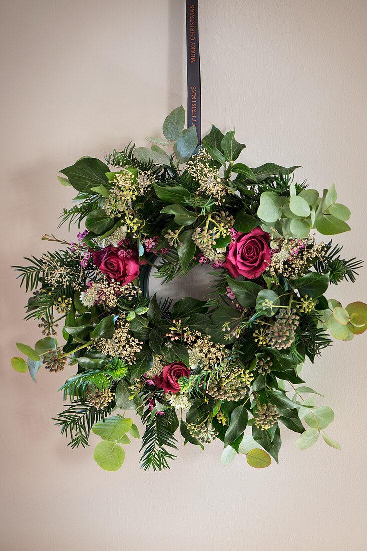 Handmade Christmas wreath with roses on wall