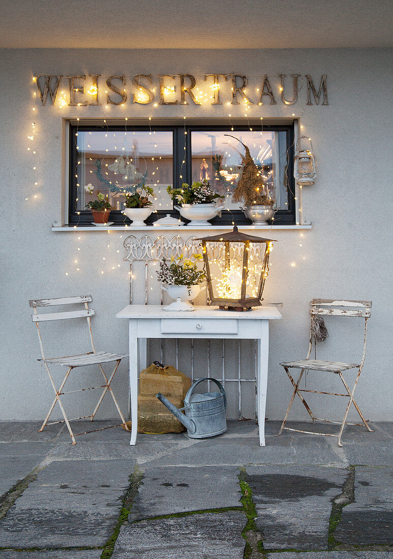 Wintry illuminated seating area on terrace outside house