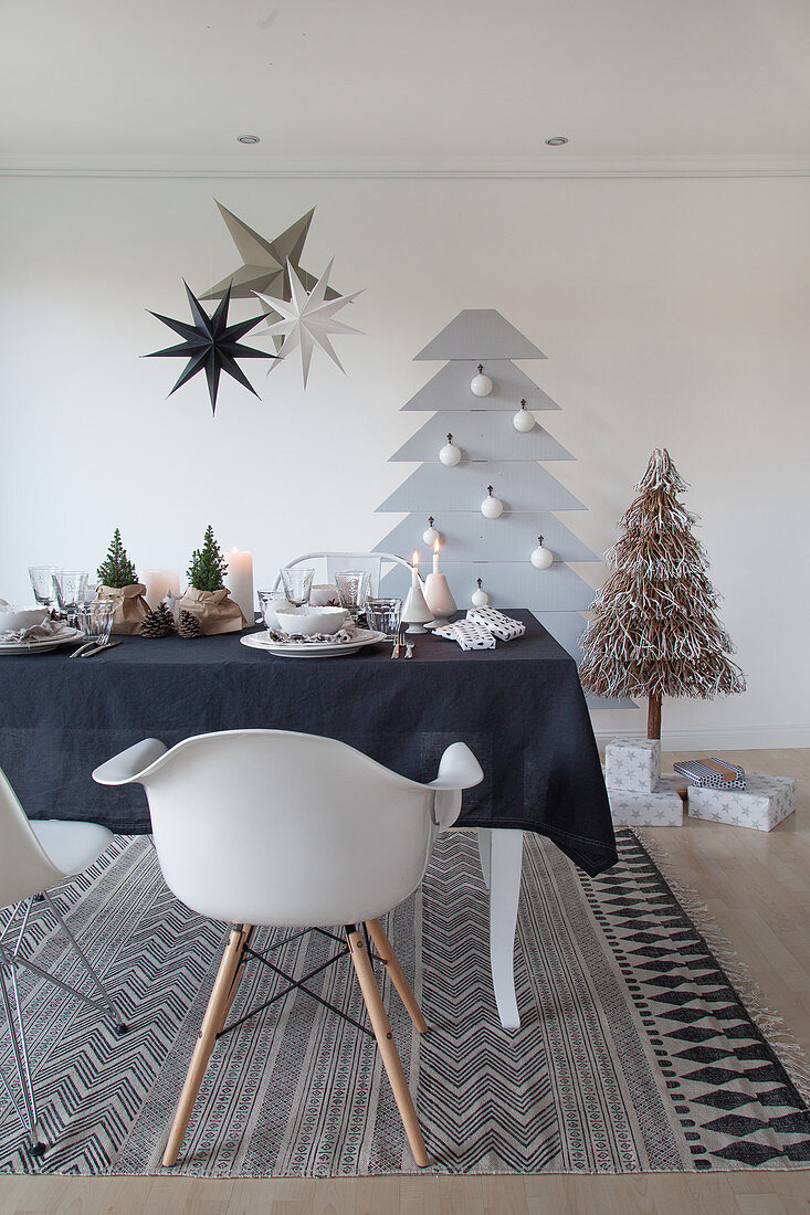 Table set for Christmas with black tablecloth in front of stylised Christmas tree on wall