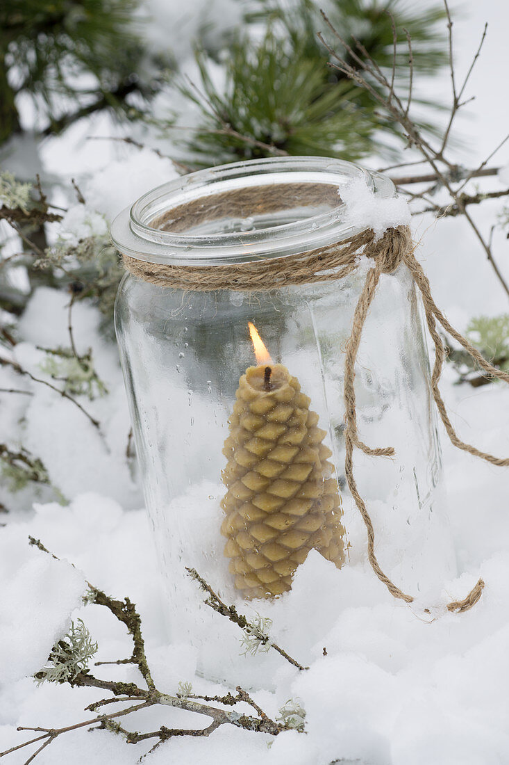 Windlicht mit Honigkerze in Tannenbaumform und Schnee