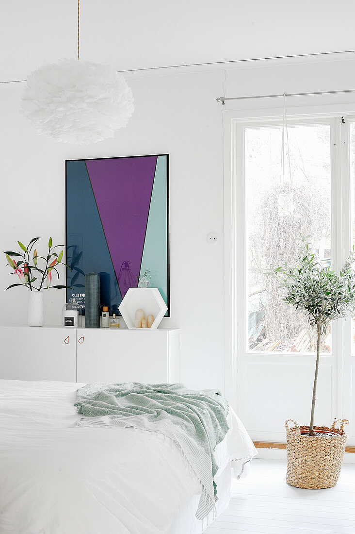Small olive tree planted in basket and boldly coloured artwork in white bedroom
