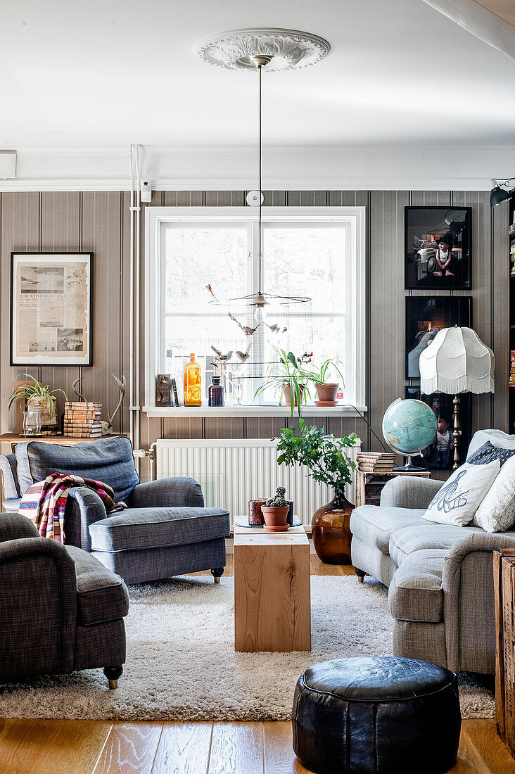 Grey couch and armchairs in living room with grey wallpaper