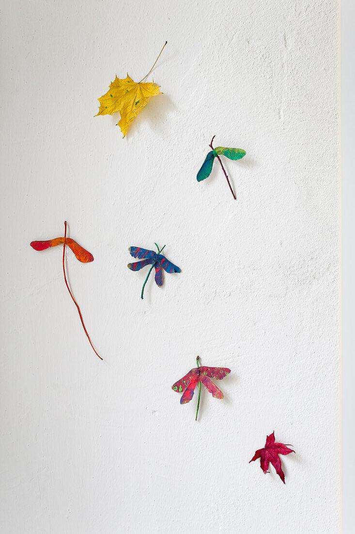 Gebastelte Libellen aus bemalten Ahornsamen an weißer Wand