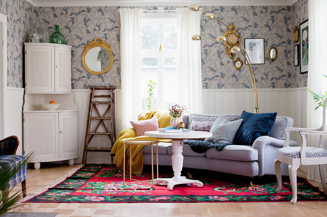 White corner cabinet, round white table and sofa on rug in living room