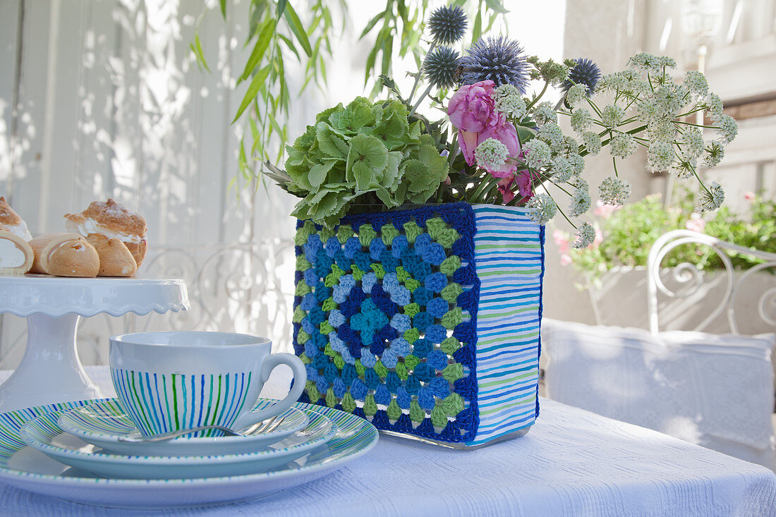 Flowers in vase with crocheted cover on set table