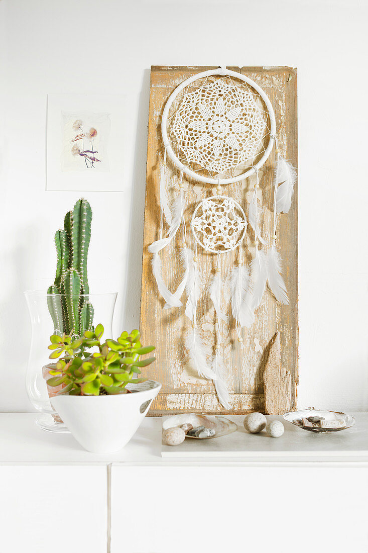 Dream-catcher made from doily and feathers next to houseplants