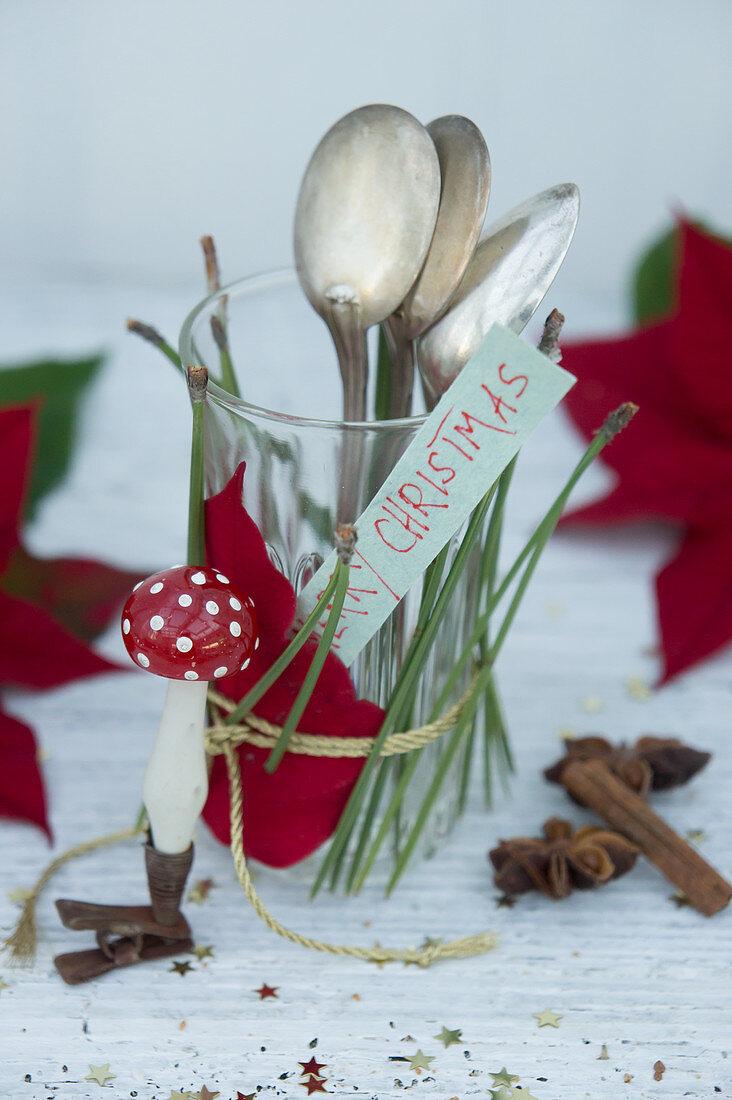 Glas mit Weihnachtsstern und Kiefernnadeln dekoriert, als Besteckhalter