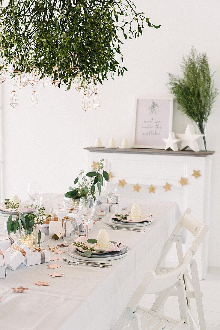 Modern gedeckter Weihnachtstisch in Weiß unterm Mistelzweig
