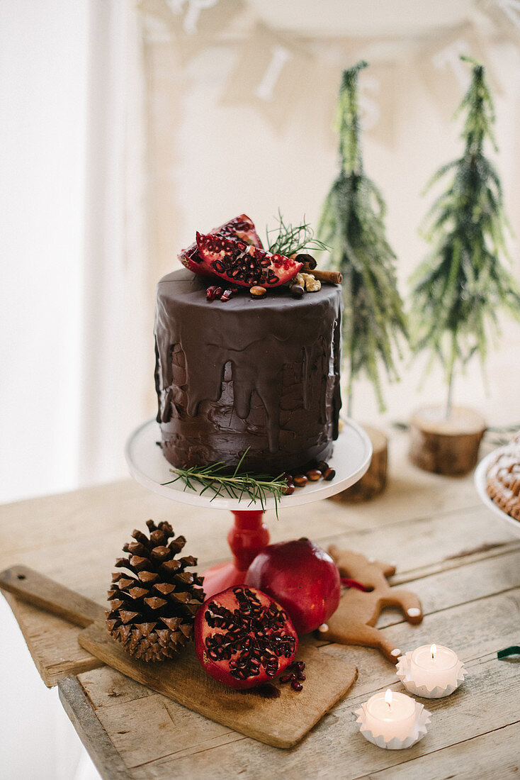 Drip cake with pomegranates and Christmas decorations