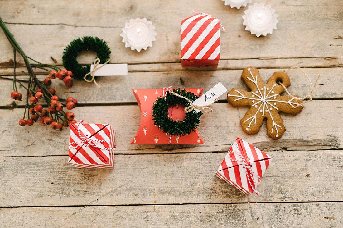 Gastgeschenk in rot-weiß gestreifter Schachtel, Lebkuchen als Baumanhänger und kleine Kränzchen