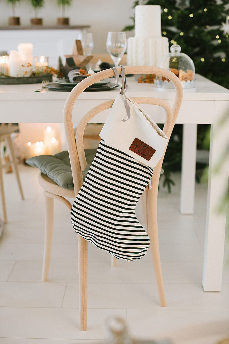Black-and-white striped Christmas stocking on chair backrest