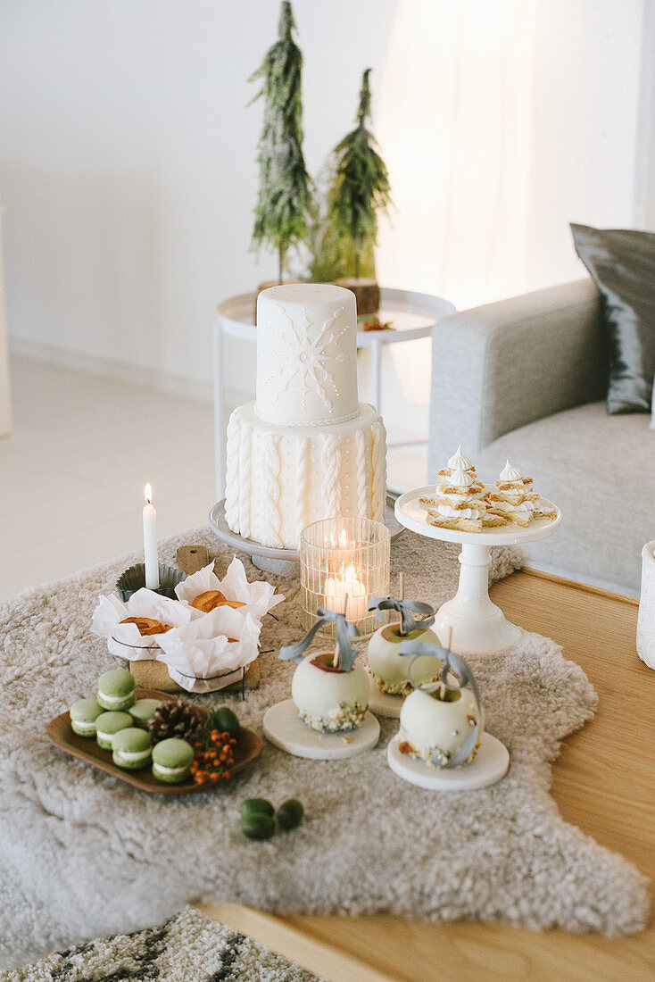 Sweet pastries and Christmas decorations on fur blanket on table