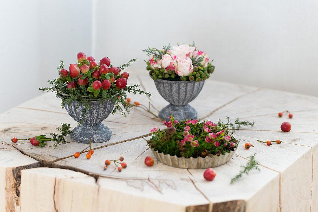 Kleine Blumengestecke in einer Backform und Metallschälchen