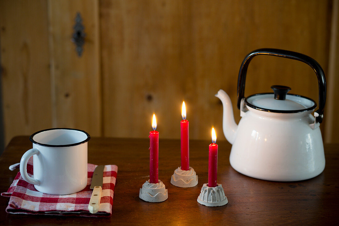Three lit red candles in cake-shaped candle holders