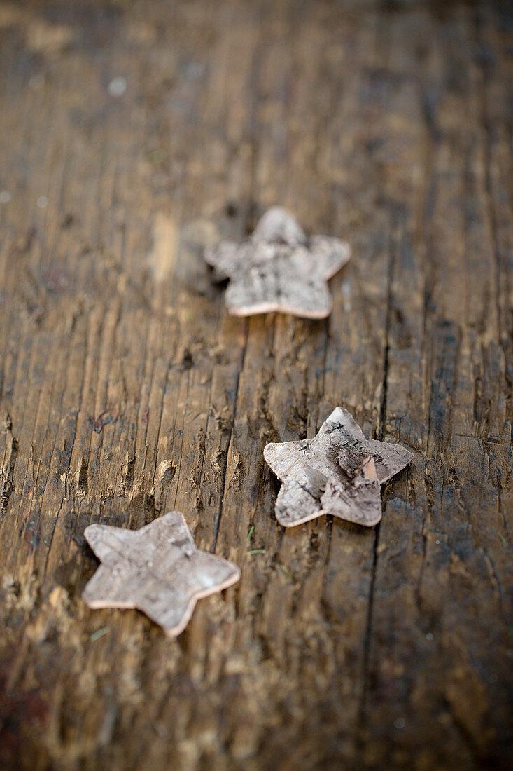 Birch-bark stars on wooden surface