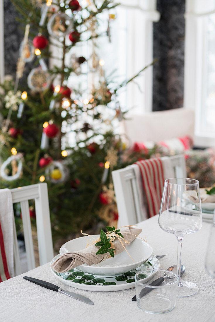 Esstisch mit festlichem Gedeck, im Hintergrund Weihnachtsbaum