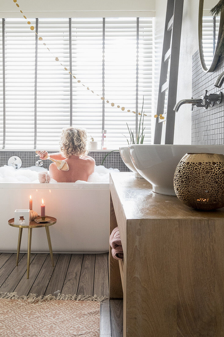 Twin countertop sinks on washstand in bathroom with Christmas decorations and woman in bathtub