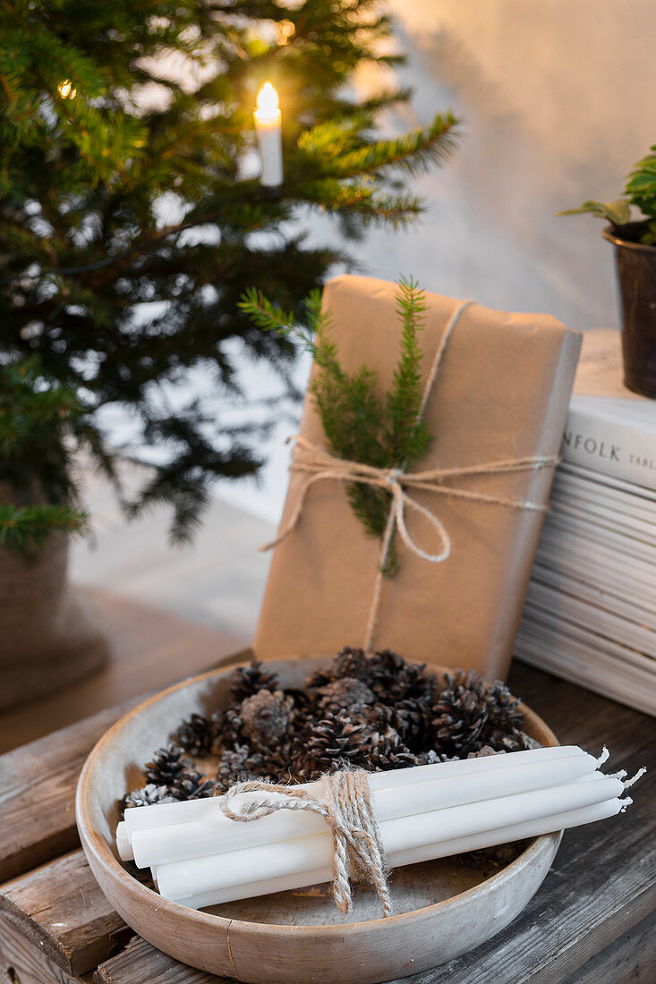 Candles and pine cones in wooden bowl and wrapped gift